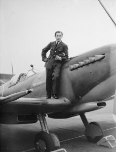 """A Czech pilot, Flight Sergeant Spacen, posing on Supermarine Spitfire LF Mark IXB, MH489 """"Red Rose II"""", at Squires Gate airport, Blackpool, Lancashire, before flying it to Biggin Hill, Kent, to join No. 485 Squadron."""